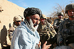 U.S. soldiers with 1st Battalion, 12th Infantry Regiment and Canadian civil affairs troops talk with an elder in the village of Ashoque in Zhari district, Kandahar province, Afghanistan.  U.S. and Canadian forces are trying to win over villagers in the district with promises of aid projects, but the effort in Ashoque has only just begun, and villagers remain wary of associating too closely with foreign troops. Dec. 2, 2009 DREW BROWN/STARS AND STRIPES