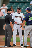 Aberdeen IronBirds manager Kevin Bradshaw (25) during the lineup exchange with Aaron Nieckula (26) and umpire Paul Roemer (left) before a NY-Penn League game against the Vermont Lake Monsters on August 19, 2019 at Leidos Field at Ripken Stadium in Aberdeen, Maryland.  Aberdeen defeated Vermont 6-2.  (Mike Janes/Four Seam Images)