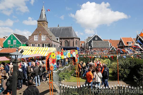 Koningsdag in Marken. Tijdens Koningsdag dragen veel inwoners van Marken klederdracht met oranje accenten. Vrijmarkt in het centrum, bij de kerk