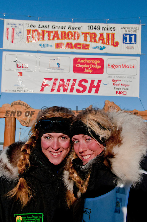Iditarod musher Kristy Berington pauses with twin sister Ana after arriving in Nome, Alaska., Iditarod 2011. This is the 26 year old's second time running and finishing the race. Kristy trains with veteran musher Paul Gebhardt in Kasilof, Alaska.