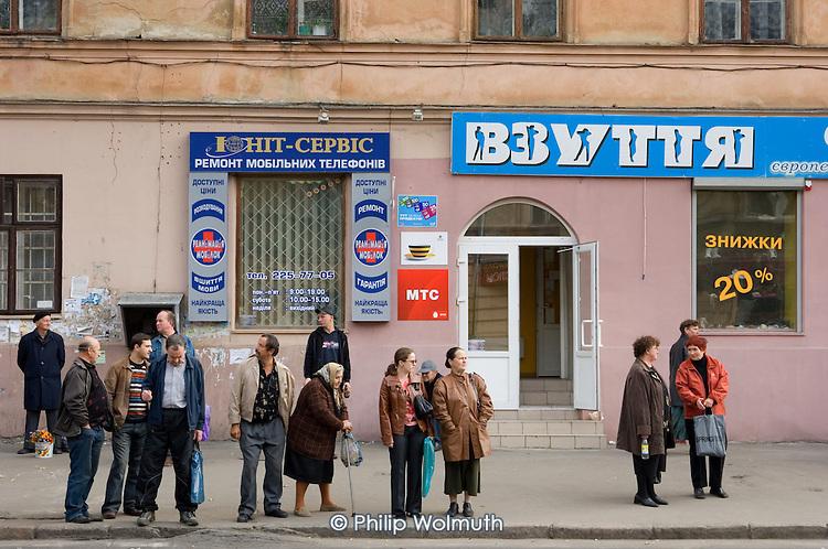 Bus queue and Cyrillic shop signs in Lviv..