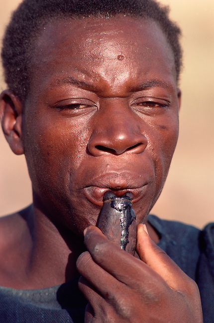 Dogon man blowing a whistle. Mali, West Africa.