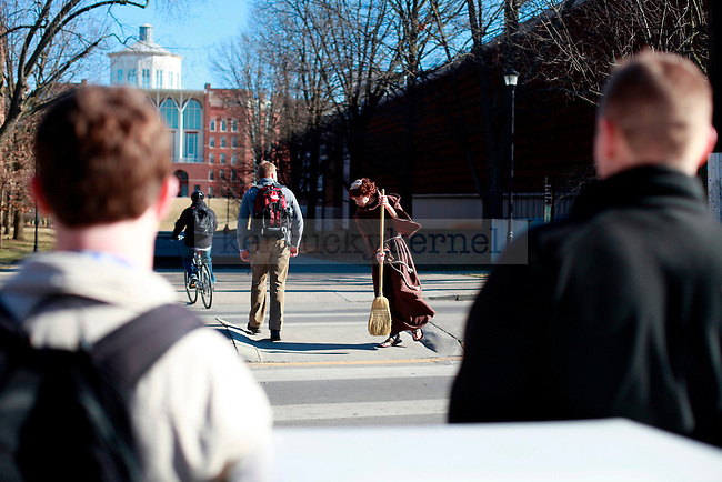 Students watch as psychology freshman Jason Baker, dressed as a monk, sweeps the pedestrian pathway in front of the Chemical Physics building on Tuesday. Every Tuesday Baker dresses up as different characters just for fun.  Photo by Zach Brake | Staff.