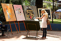 Young woman looking at paintings for sale at the art show held every Sunday in the Jardin del Arte, Sullivan Park, Mexico City