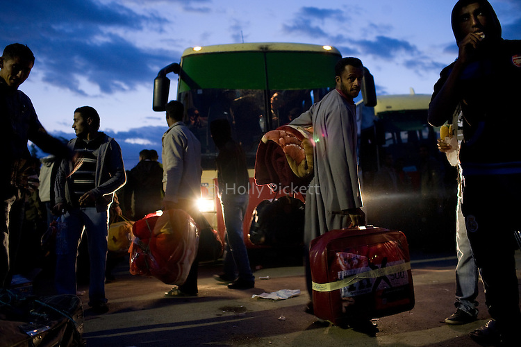 Men wait for a bus bound for the Tunis airport, at the border crossing with Libya near Ben Guerdane, Tunisia, Thursday, Feb. 24, 2011. Foreign nationals, including many Egyptian workers, fled Libya as Col. Muammar Qaddafi tried to maintain his grip on the capital Tripoli. In the latest uprising to strike the Middle East, street protests which began in Eastern Libya spread to Tripoli, as opposition members called for Qaddafi to follow Tunisian president Zine el-Abidine Ben Ali and Egyptian president Hosni Mubarak and step down.