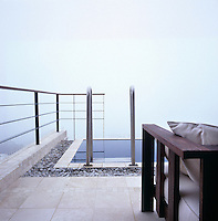Infinity pool sits along the edge of Table Mountain with a misty sea view beyond