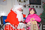 Santa's Gift : Lily Mai Moynihan, Rathea, Listowel receiving her gift from Santa Claus at the Seanachi Centre in Listowel on Sunday last.