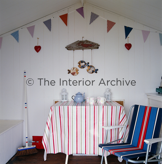 The interior of the beach hut has a retro feel with a candy-striped tablecloth on the table and bunting decorating the walls