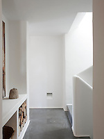 The stark, white hallway has a grey, concrete floor and soft lines. Built-in storage houses logs  for the fire