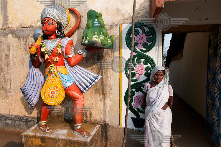 A woman stands at the entrance of a temple next to a statue of Ganesha in the village of Jojo.