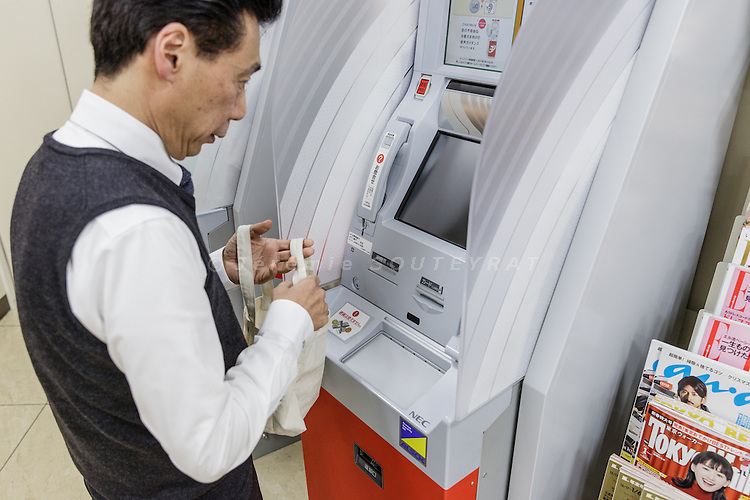 Tokyo, Japan, December 16 2016 - Mr Shinichi YOKOYAMA, owner of three Seven-Eleven convenience stores, is stocking the ATM with the cash from the cash register. <br /> Seven Bank is a bank that has all its ATMs in 7-Eleven convenience stores and is making a lot of money by charging fees for ATM users. This is a contrast to other banks that are struggling to make profits.