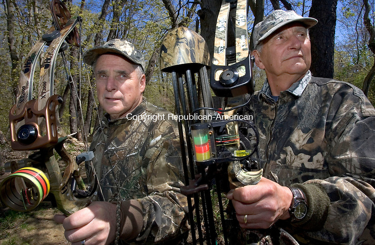 WATERTOWN CT. 03 May 2013-050313S01-From left, George Dunn of Waterbury and Gene Hubeny of Watertown grab their bows in Hubeny's backyard after hunting in Watertown Friday..Steven Valenti Republican-American