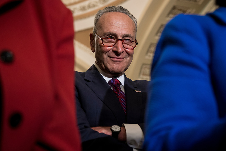UNITED STATES – July 10: Senate Minority Leader Charles Schumer, D-N.Y., listens as Sen. Amy Klobuchar, D-Minn., left, and Sen. Mazie Hirono, D-Hawaii, right, speak to the press after the Senate Democrats' policy lunch in the Capitol on Tuesday, July 10, 2018.  (Photo By Sarah Silbiger/CQ Roll Call)