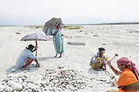 India – West Bengal: Bishmoni Tanti (second from right), 45, crushing pebbles and stones along the Diana riverbed at Red Bank Tea Estate, in the Dooars region. The garden, which houses 888 workers out of a population of 5,000 people, has been closed since 2013. With no more income, food rations and health services, its workers resorted to stonecrushing in order to survive. Tanti now earns a paltry 333 rupees per week. During the monsoon season, when the water fills the riverbed, she looks for employment as a temporary worker in other tea gardens. Her family is now surviving on emergency food rations provided by the government.