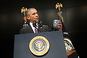 United States President Barack Obama holds up a jar of paper chips as he joking talks about meeting with Director of National Intelligence James Clapper as he speaks at a ceremony marking the 10th anniversary of the formation for the Office of the Director of National Intelligence, at it's headquarters on April 24, 2015 in McLean, Virginia. I<br /> Credit: Kevin Dietsch / Pool via CNP
