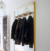 In the entrance hall a large retro mirror with an integral coat-rack is hung with a selection of denim jackets