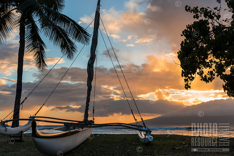 Sunset over a Hawaiian sailing canoe on a beach in Lahaina, Maui, with Lana'i in the distance.
