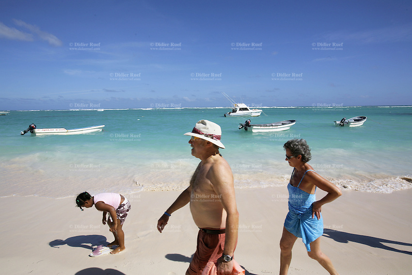 Dominican Republic. La Altagracia Province. Coastal resort of Punta Cana. Playa Bavaro. El Cortecito. A couple of white tourists walks on the beach. a young black girl plays with water in the sand.Blue sky. Punta Cana is well-known for its beaches  where meet whites sands and warm turquoise water from the Atlantic Ocean.  © 2006 Didier Ruef
