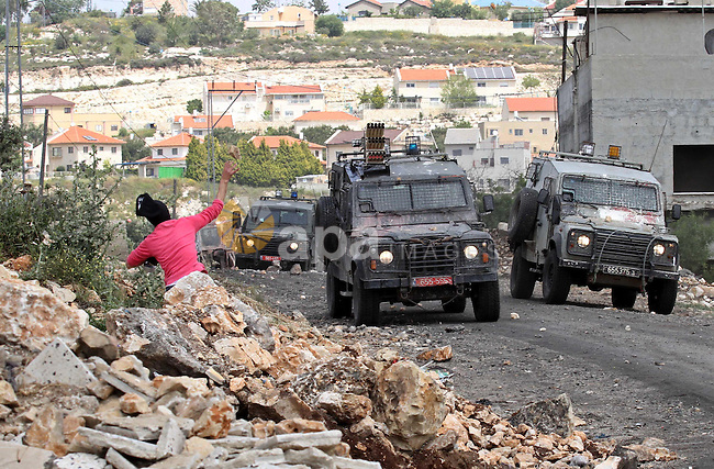 A Palestinian protester throws stones towards Israeli security forces during clashes following a protest Palestinian Prisoner's Day and against the expropriation of Palestinian land by Israel in the West Bank village of Kafr Qaddum, near the northern city of Nablus, April 17, 2015. The current number of Palestinians held in Israeli prisons is at least 6,200 and is the biggest for at least five years, according to figures from rights groups. Photo by Nedal Eshtayah