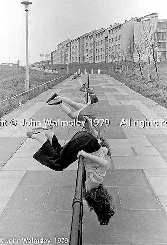 Playing on the railings, Wester Hailes, Scotland, 1979.  John Walmsley was Photographer in Residence at the Education Centre for three weeks in 1979.  The Education Centre was, at the time, Scotland's largest purpose built community High School open all day every day for all ages from primary to adults.  The town of Wester Hailes, a few miles to the south west of Edinburgh, was built in the early 1970s mostly of blocks of flats and high rises.