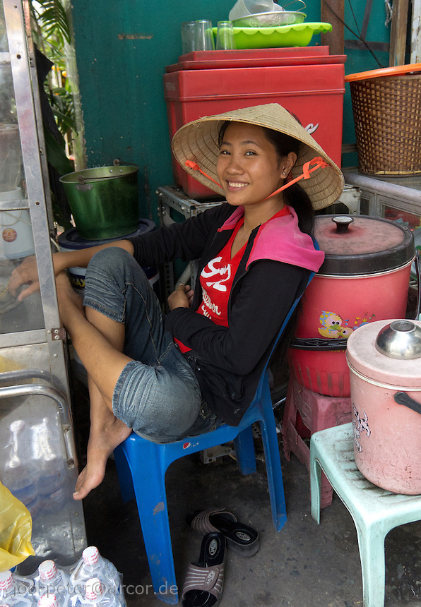 woman with traditional leaf-hat selling fruits in the streets of Saigon relaxes on  a chair, Ho Chi Minh City / Saigon,  Vietnam