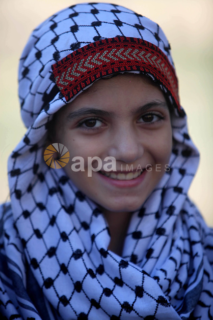 A Palestinian girl wears a traditional dress as she poses for a photo as she takes part in a rally marking the Palestinian traditional customs day, in Gaza City, on July 30, 2019. Photo by Mahmoud Ajjour