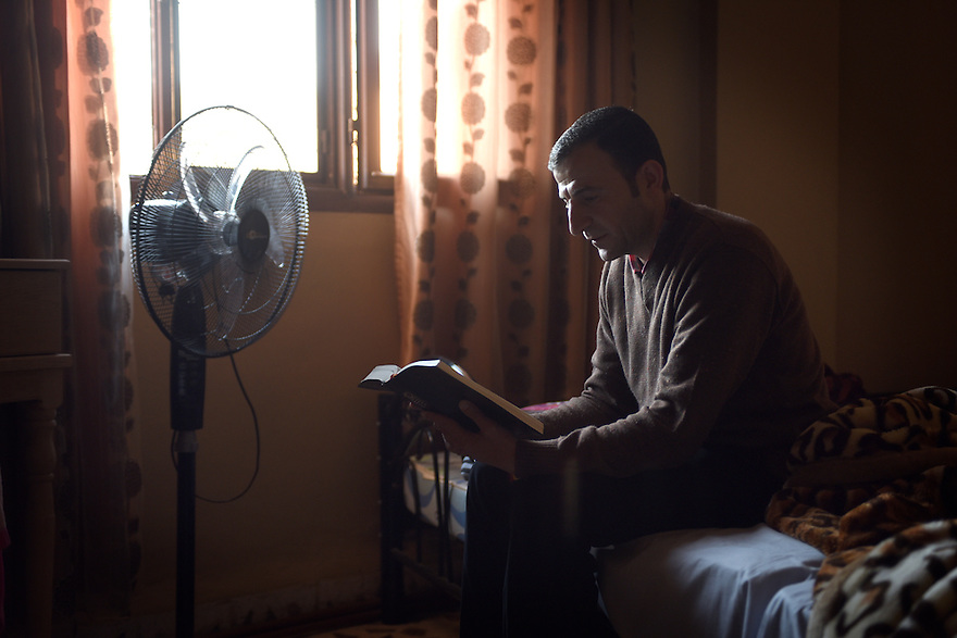 TRAUMA HEALING CASE STUDIES IN JORDAN. RAFED SAKAT, 39, FROM KARAKOUSH, IRAQ, READS FROM THE BIBLE IN HIS NEW HOME IN MADABA, JORDAN. 20/04/16, PHOTO BY CLARE KENDALL.