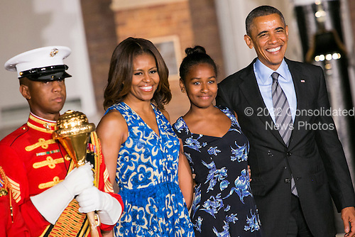 First Lady Michelle Obama, left center, daughter Sasha Obama, right center, and United States President Barack Obama, right, attend the Marine Barracks Washington, D.C. Evening Parade in Washington, D.C., on Friday, June 27, 2014. <br /> Credit: Kristoffer Tripplaar  / Pool via CNP