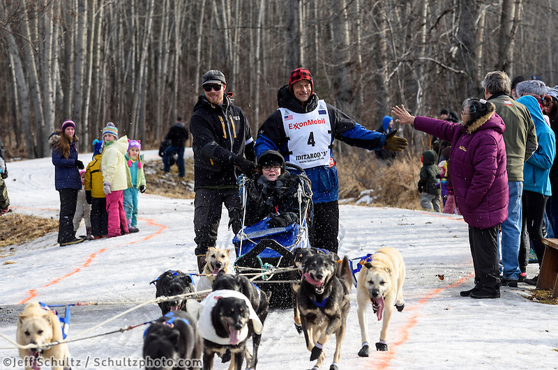 Martin Buser and team run past spectators on the bike/ski trail with an Iditarider in the basket during the Anchorage, Alaska ceremonial start of the 2015 Iditarod race. Photo by Ed Bennett/IditarodPhotos.com