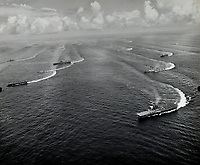 """U.S. Navy Task Force 38 aircraft carriers and other ships turns in unison near Tokyo, two days after the WWII cease fire is called. USS Wasp in right foreground and USS Shangri-La in middle left. Task Force 38 had ten fleet carriers and six light carriers for 16 total. - Aug. 17, 1945<br /> <br /> Photo by """"Scoop"""" and Keslin of the USS Shangri-La"""