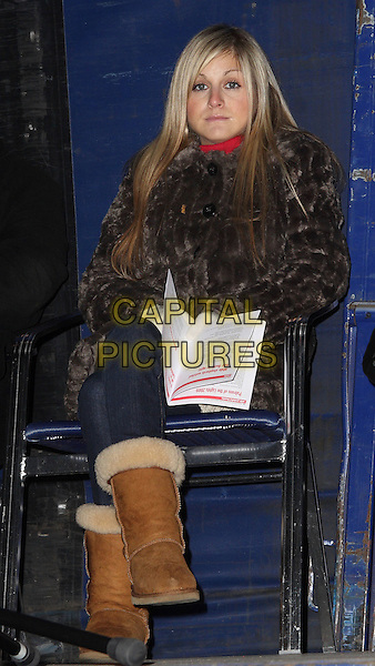 NIKKI GRAHAME .Big Brother 7's Nikki Grahame switches the Christmas Lights on in the Bedfordshire market town of Biggleswade, Bedfordshire, England, UK, December 4th 2009.xmas BB7 full length gloves brown fur coat chestnut uggs ugg boots jeans sitting down .CAP/JIL.©Jill Mayhew/Capital Pictures
