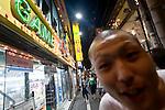 A man looks into the lens of the camera as he walks down the main shopping street in Shimokitazawa, Setagaya Ward, Tokyo, Japan..Photographer: Robert Gilhooly