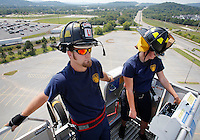 NWA Democrat-Gazette/DAVID GOTTSCHALK  Ryan Powers (left), a driver, and Andi Mooneyham, a probationary firefighter, both with the city of Fayetteville Fire Department, raise the ladder platform to 114 feet Monday, August 31, 2015 during a weekly truck check in Fayetteville. The Ladder One truck is run through an operation and maintenance check that includes  all ladder functions, engine maintenance and check of other operations.
