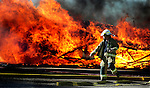MICHAEL SMITH/WTE.Cheyenne firefighter Ken Aitchison hurries past a trailer engulfed in flames to get some equipment while crews battle the morning blaze at Big Country Estates on South Greeley Highway.