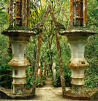 Weathered columns either side of a symbolic archway herald a pathway through the garden