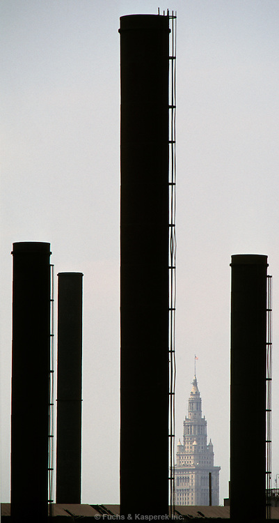 The smokestacks of a steel mill frame the Terminal Tower building in downtown Cleveland, OH.