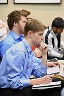 A student listens attentively to a lecture while taking notes.
