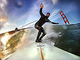 USA, California, San Francisco, Fort Point, surfer on a wave at Fort Ponit Surf Break below the Golden Gate Bridge at sunset