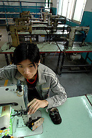 Empty benches behind a worker at Jet Shoe Manufacturing in Houjie Town, Dongguan, China. Jet is struggling to find workers and is running at half capacity and employing many older men rather than young women. As the economy changes and Chinese labour gets more expensive, factories are closing leaving ghost towns behind them..20 Dec 2007.