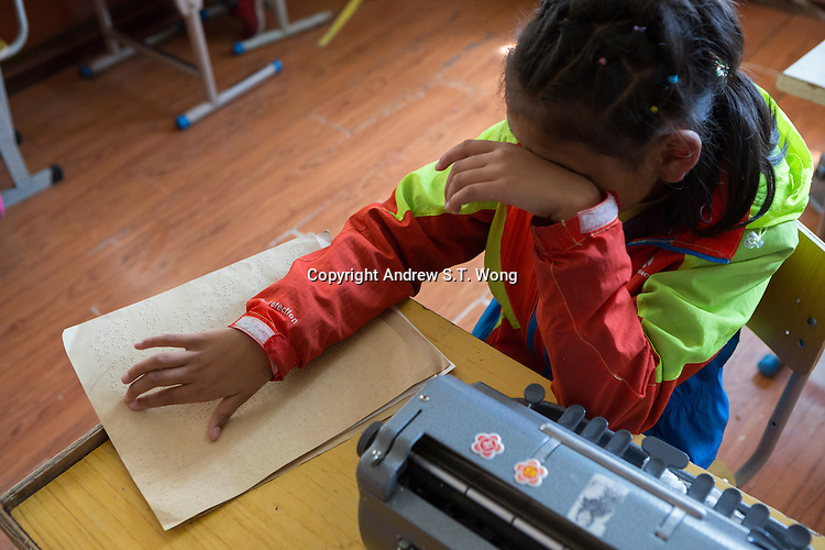 A visually impaired Tibetan student reads braille during a lesson at the School for the Blind in Tibet, in the capital city of Lhasa, September 2016.