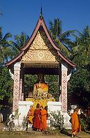 Asie/Laos/ENV Ventiane/Luang Prabang: Vat Xieng Thong jeunes bonzes devant la statue de Boudha