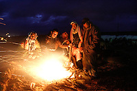 Egyptian refugees huddle around a fire to stay warm. Tens of thousands of people, mainly Egyptian workers, fled unrest in Libya and crossed the border into Tunisia. Some slept in the open for several days before being processed.  At the same time forces loyal to Col. Gaddafi fought opposition forces in various parts of the country.