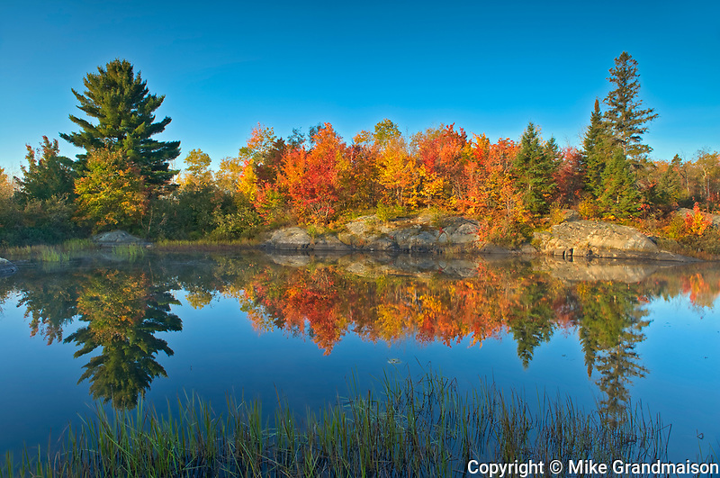 Reflection of autumn colors  in St. Poithier Lake<br /><br />Ontario<br />Canada