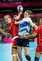 28 JUL 2012 - LONDON, GBR - Kathryn Fudge (GBR) of Great Britain (centre) finds her path to goal blocked by Suzana Lazovic (MNE) of Montenegro (left, in red and gold) during the women's London 2012 Olympic Games Preliminary round handball match at The Copper Box in the Olympic Park, in Stratford, London, Great Britain .(PHOTO (C) 2012 NIGEL FARROW)