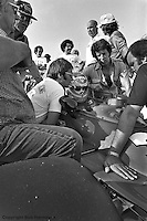 INDIANAPOLIS, IN: Clay Regazzoni sits in his McLaren M16C 4/Offenhauser TC while Mario Andretti (seated, right) offers advice before practice for the Indianapolis 500 on May 29, 1977, at the Indianapolis Motor Speedway.