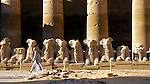 Man walking in front of statues, Luxor, Egypt