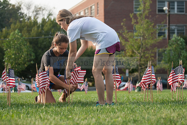UK Air Force ROTC members Brianna Arnold (left) and Alexis Gill straighten some American flags for the September 11th memorial ceremony in front of UK's visitor center in Lexington, Ky., on Wednesday, September 10, 2014. Photo by Adam Pennavaria | Staff