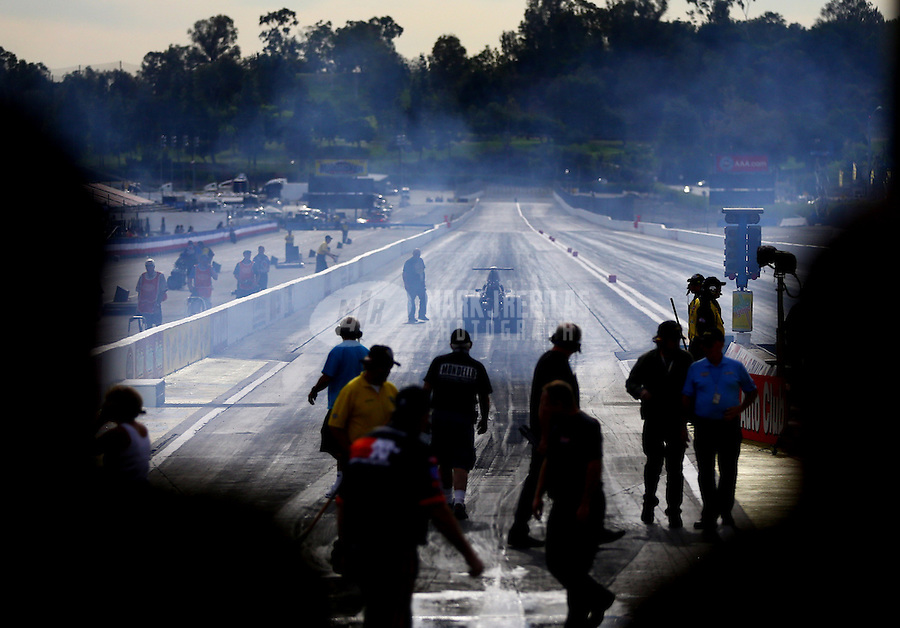Nov 7, 2013; Pomona, CA, USA; An NHRA comp eliminator driver backs up from his burnout during qualifying for the Auto Club Finals at Auto Club Raceway at Pomona. Mandatory Credit: Mark J. Rebilas-
