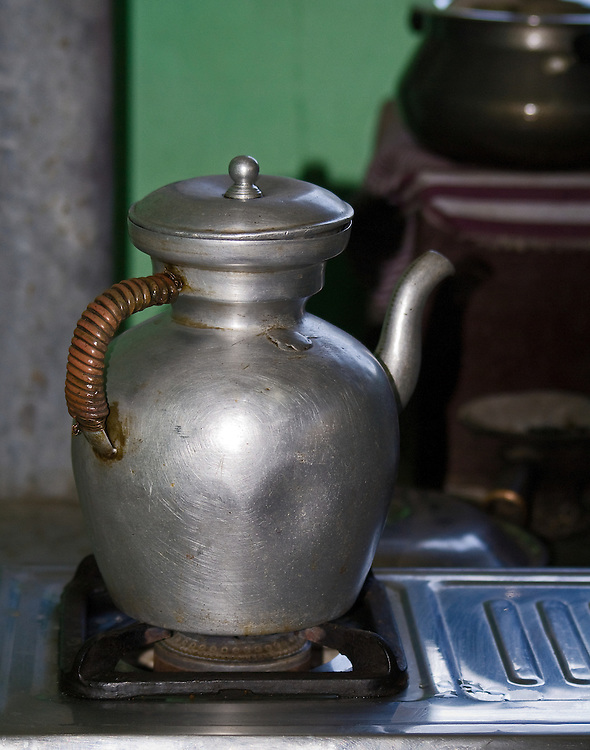 This metal tea kettle with its wrapped handle sitting on the old fashion burner in a home of a Bhutanese family is symbolic of travels throughout this and other countries traveled where the kettle is ALWAYS ON ready to welcome guests with a cup of tea.