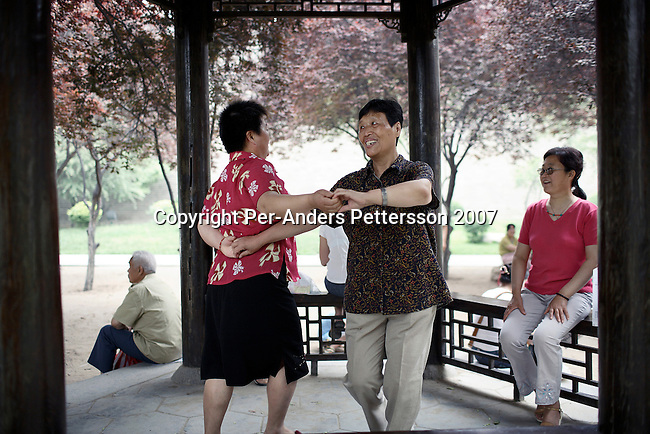 XIAN, CHINA - JUNE 3: Unidentified women dance in a park on June 3, 2007 in central Xian, China. Many retired people come to the park to exercise, usually early in the morning. The city has about 3,3 million inhabitants and is the capital of Shaanxi province in China. It was the eastern terminus for the Silk Road and the location for the Terracotta Army during the Qin Dynasty. Its history dates back more than 3,100 years. (Photo by Per-Anders Pettersson)...
